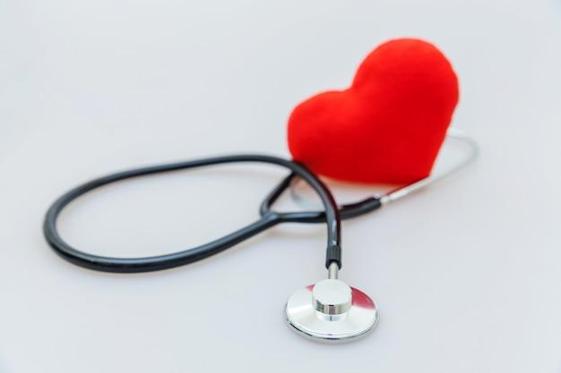 Estetoscópio de equipamento de medicina ou estetoscópio e coração vermelho isolado. dispositivo de instrumento para médico. seguro de vida em assistência médica