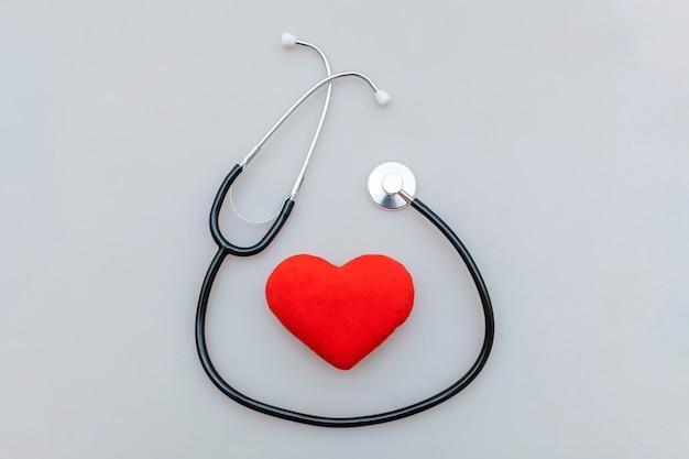 Estetoscópio de equipamentos de medicina e coração vermelho isolado no fundo branco