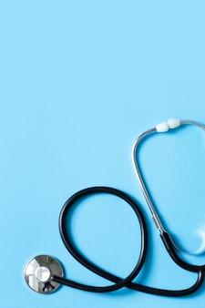 Estetoscópio de metal para diagnóstico médico em fundo azul. fundo do conceito médico e de saúde. foto vertical