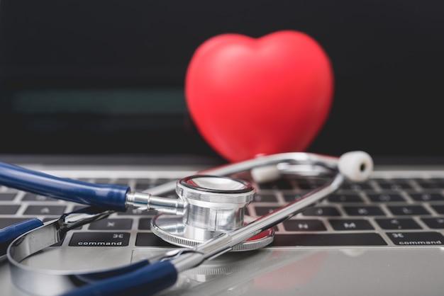 Estetoscópio de saúde e coração vermelho no teclado do computador portátil