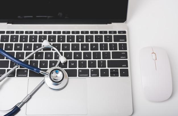 Estetoscópio de saúde no teclado do computador portátil