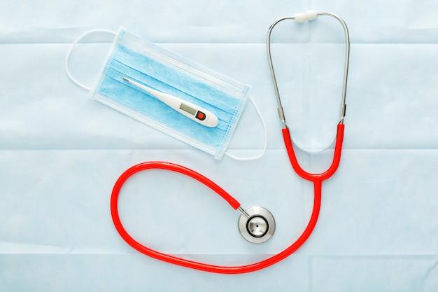 Estetoscópio de termômetro de máscara médica vermelha, máscara de proteção cirúrgica em azul.