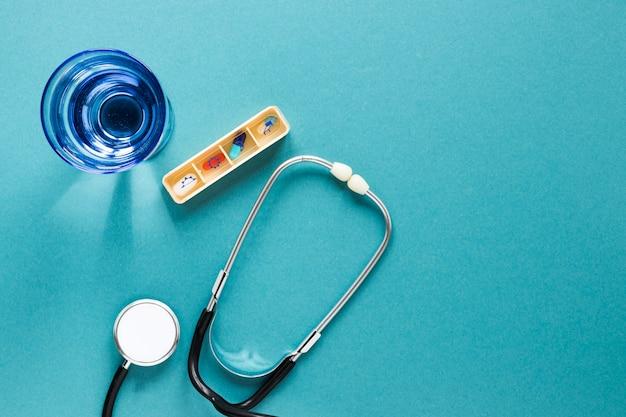 Estetoscópio de vista superior com caixa de comprimidos e copo de água