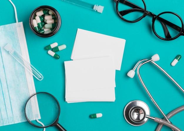 Estetoscópio de vista superior com medicamento em cima da mesa