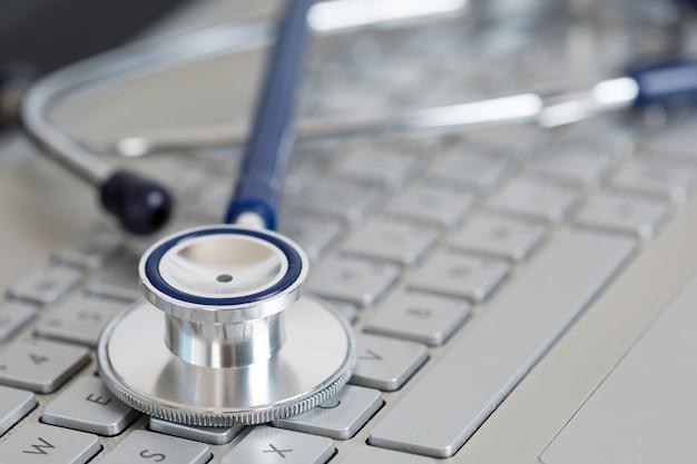 Estetoscópio deitado no close up do teclado do laptop. conceito médico. medicina moderna e conceito de equipamento de alta tecnologia