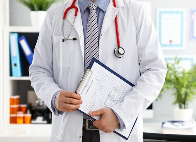 Estetoscópio deitado no peito do médico masculino no escritório. médico loja física e prevenção de doenças do paciente er consultor body