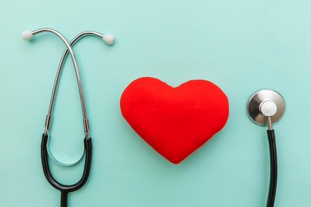 Estetoscópio do equipamento da medicina e coração vermelho isolados no azul pastel na moda