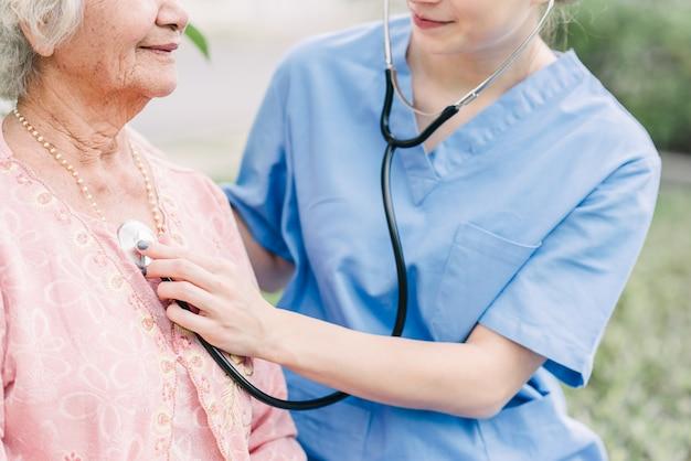 Estetoscópio do uso do cuidador à verificação da mulher idosa