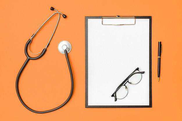 Estetoscópio e caderno laranja