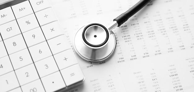 Estetoscópio e calculadora. conceito de custos de saúde ou seguro médico