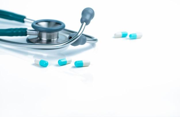 Estetoscópio e comprimidos azul-brancos da cápsula na tabela do doutor ou na mesa da enfermeira. exame completo de saúde.