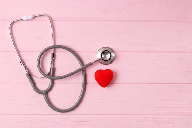 Estetoscópio e coração com fundo de cor de madeira. saúde, medicina. foto de alta qualidade