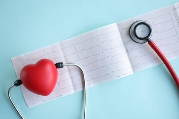 Estetoscópio e coração de brinquedo vermelho no eletrocardiograma em close up de fundo azul