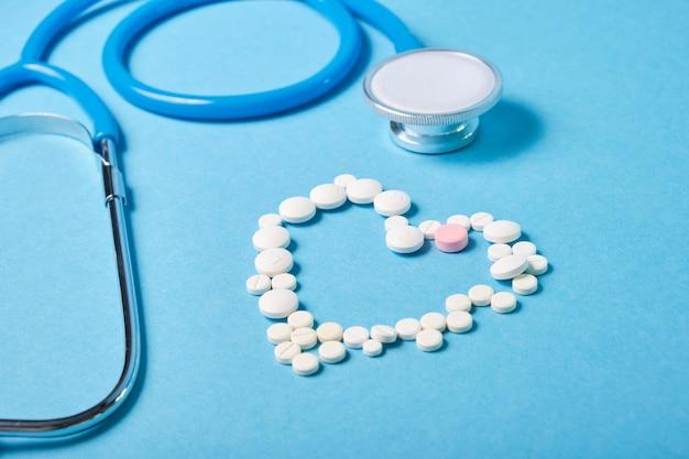 Estetoscópio e coração de pílulas na superfície azul