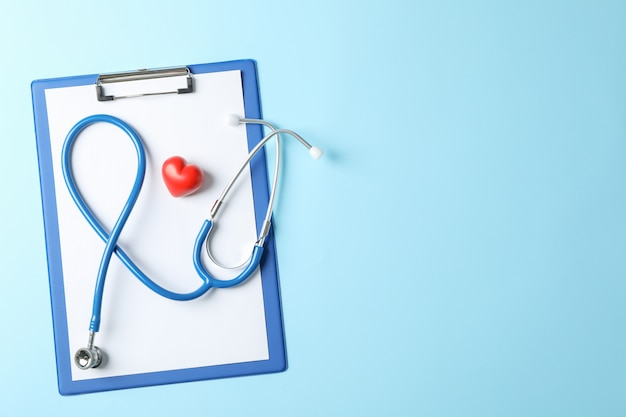 Estetoscópio e coração em fundo azul, espaço para texto