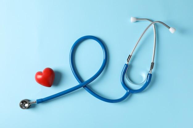 Estetoscópio e coração em fundo azul, vista superior