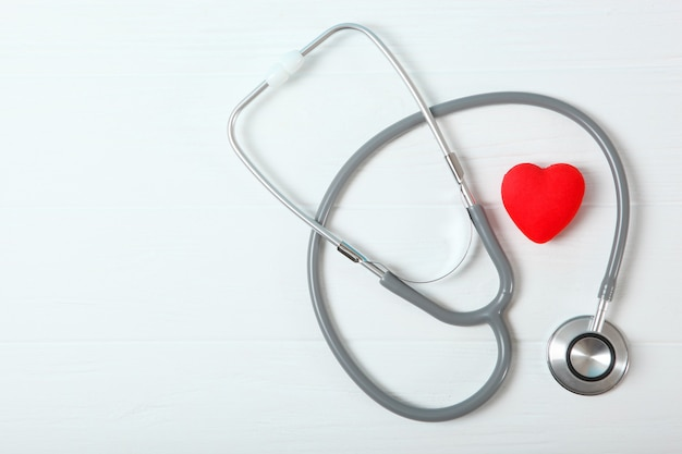 Estetoscópio e coração em fundo de madeira saúde medicina