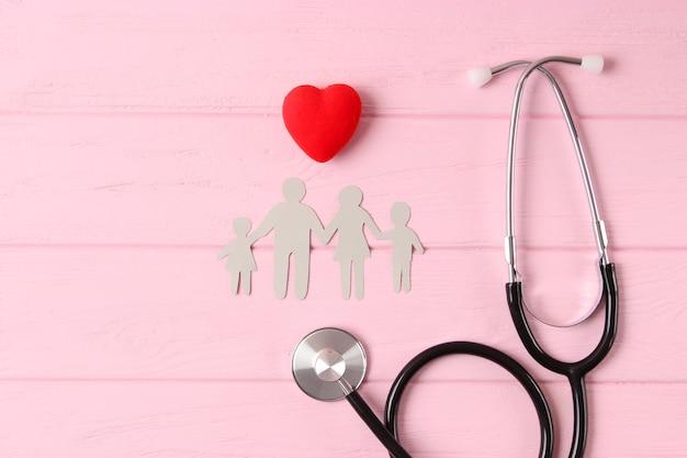 Estetoscópio e coração em uma vista superior de fundo colorido. medicina familiar. foto de alta qualidade Foto Premium