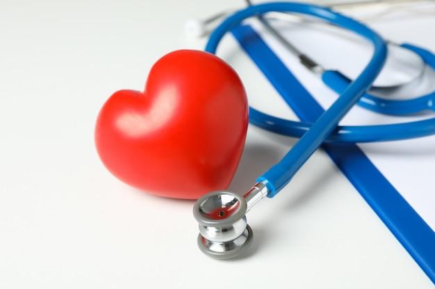 Estetoscópio e coração na superfície branca, close-up