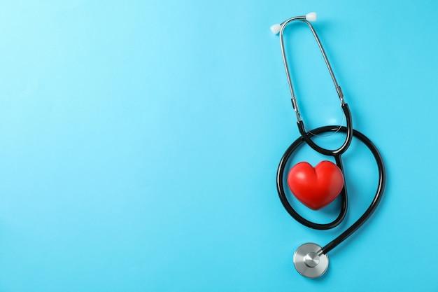 Estetoscópio e coração sobre fundo azul, espaço para texto. cuidados de saúde