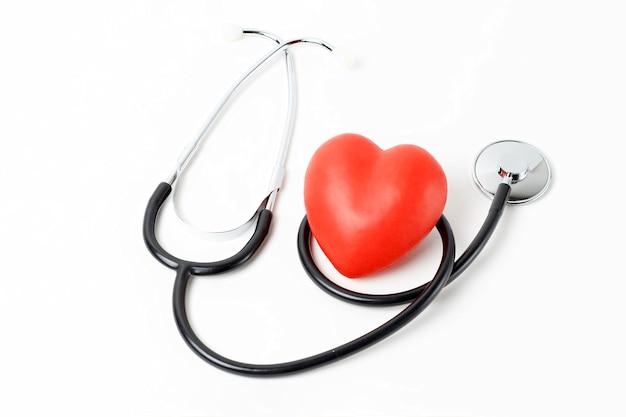 Estetoscópio e coração vermelho close-up no fundo branco