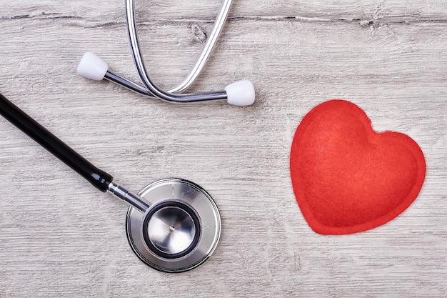 Estetoscópio e coração vermelho. dispositivo médico em pano de fundo de madeira. controle de pressão arterial.