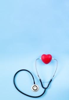 Estetoscópio e coração vermelho em cima de fundo azul claro com espaço para texto