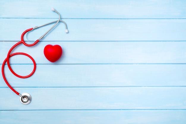 Estetoscópio e coração vermelho em madeira azul