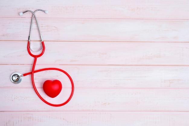 Estetoscópio e coração vermelho em madeira rosa
