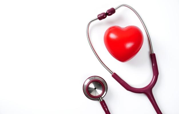 Estetoscópio e coração vermelho isolado no fundo branco cuidados com o coração