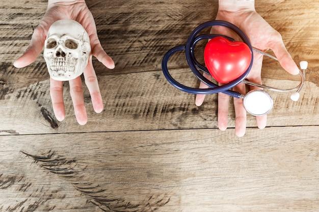 Estetoscópio e coração vermelho na mão esquerda, crânio na mão direita. escolhendo cuidados de saúde e morrer c