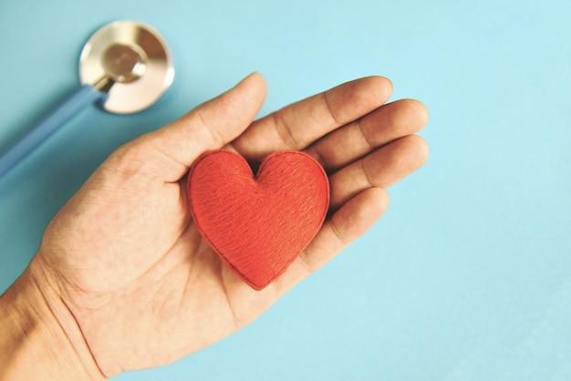 Estetoscópio e coração vermelho na mão