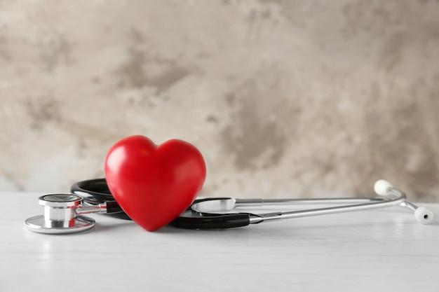 Estetoscópio e coração vermelho na mesa