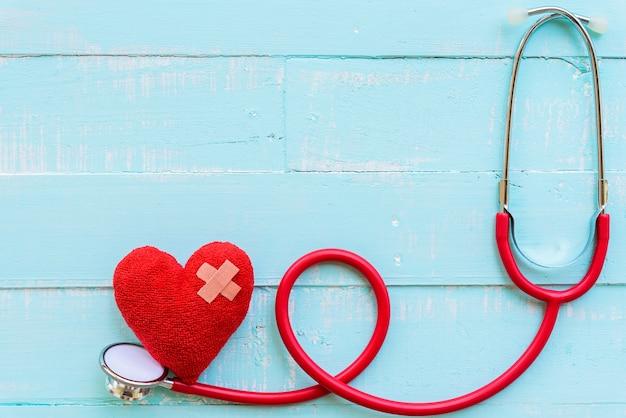 Estetoscópio e coração vermelho na textura de fundo azul mesa de madeira.