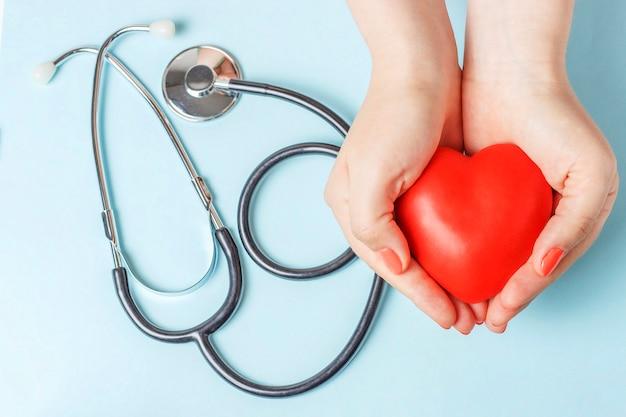 Estetoscópio e coração vermelho nas mãos femininas close-up em fundo azul