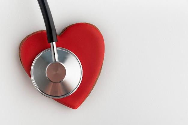 Estetoscópio e coração vermelhos fecham sobre fundo branco. conceito de doença cardíaca.