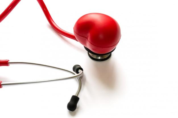 Estetoscópio e coração vermelhos na membrana isolada no branco. diagnóstico e tratamento em cardio
