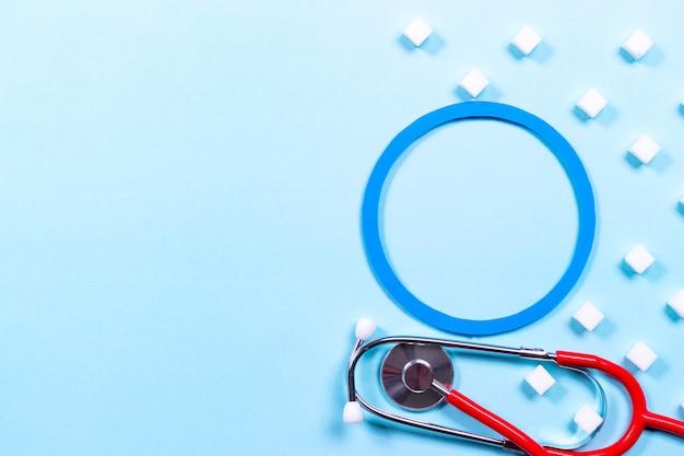 Estetoscópio e cubo de açúcar sobre fundo azul pastel. conceito de dia mundial do diabetes