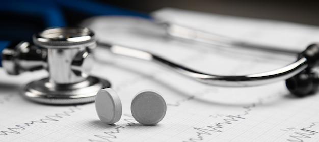 Estetoscópio e dois comprimidos na borda de mentira em uma folha com um eletrocardiograma