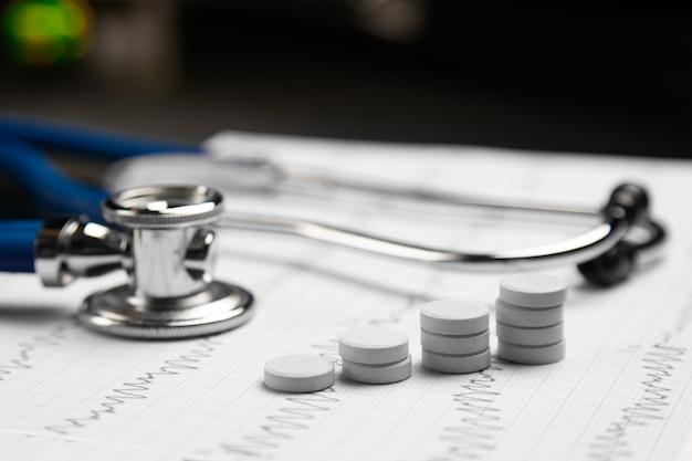 Estetoscópio e escadas de comprimidos deitar na folha com eletrocardiograma