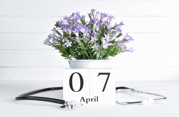 Estetoscópio e flores roxas em uma panela com o calendário de bloco de madeira de texto de 7 de abril