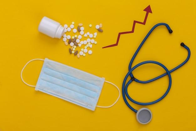 Estetoscópio e frasco de comprimidos com seta de crescimento tendendo para cima em amarelo