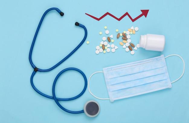 Estetoscópio e frasco de comprimidos, máscara facial com seta de crescimento tendendo para cima em um azul