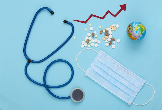 Estetoscópio e frasco de comprimidos, máscara facial, globo com seta de crescimento tendendo para cima em um azul