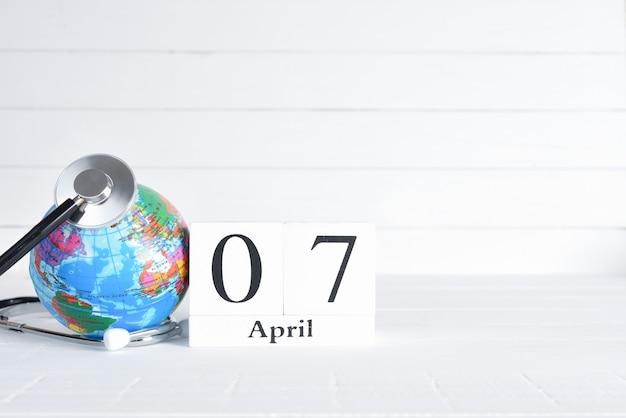 Estetoscópio e globo com calendário de bloco de madeira de 7 de abril de texto sobre fundo branco de madeira.