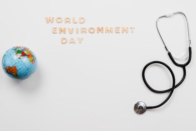Estetoscópio e globo com o texto do dia de ambiente de palavra