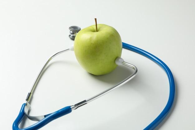 Estetoscópio e maçã em fundo branco, close-up