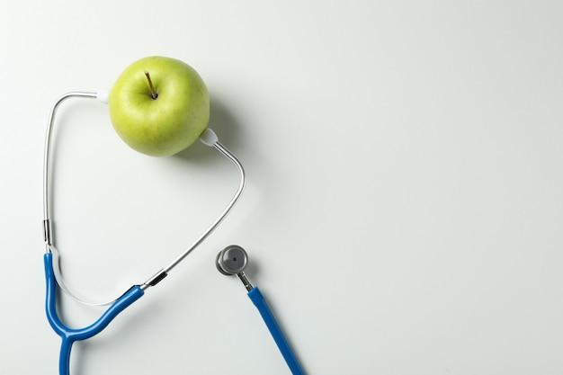 Estetoscópio e maçã em fundo branco, espaço para texto