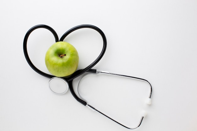 Estetoscópio e maçã verde plana leigos