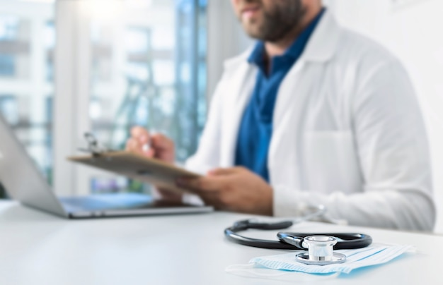 Estetoscópio e máscara médica na mesa dos médicos em segundo plano. médico conduz uma consulta on-line ao paciente usando um laptop. conceito de medicina online